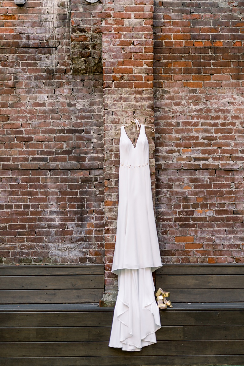 v-neck allure bridal gown of silk crepe hanging on brick wall