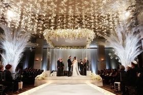 bride and groom standing under chuppah white decor butterfly lucite column