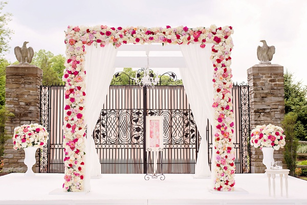 wedding ceremony decor white four post ceremony structure pink and ivory flowers outdoor ceremony