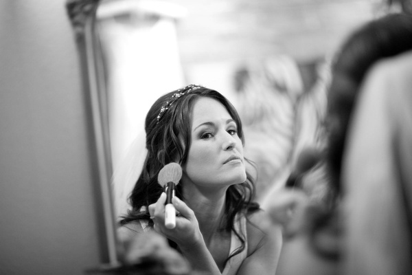 Black and white photo of bride getting ready in front of mirror