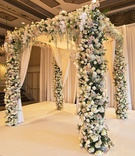 chuppah with floral columns and canopy with drapery accents