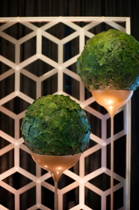 spherical arrangements of foliage resting in long copper stands in front of geometric backdrop
