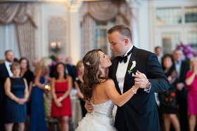Bride in a strapless Lazaro dress with beaded bodice dances with groom in black tuxedo