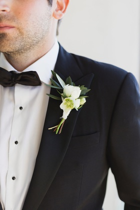 groom boutonniere with white flowers with dark green leaves