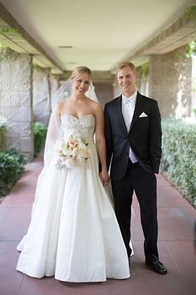 Bride in Anne Barge ball gown and veil holds hand of groom in black tuxedo at Arizona Biltmore