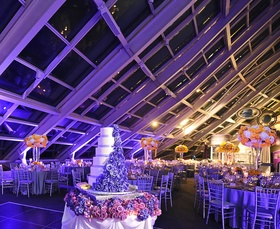 Wedding reception cake decorated with violet sugar roses, purple lighting, yellow & white flowers