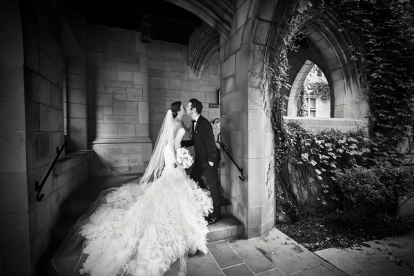 black and white photo of bride and groom kissing stone walls greenery classic chicago wedding