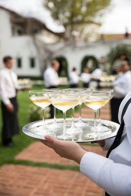 wedding reception welcome drink champagne in glass coupe glass on silver tray walkway to reception