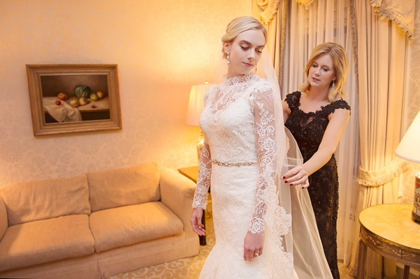 Bride in wedding dress with lace over top gets ready with her mom on wedding day