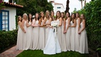 Bride in white a line wedding dress and bridesmaids in ivory beige floor length dresses white flower