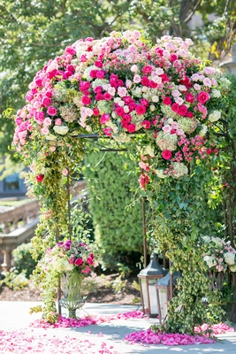 Pink rose, hot pink rose, greenery on domed garden pergola arch with lanterns and urns flower petals