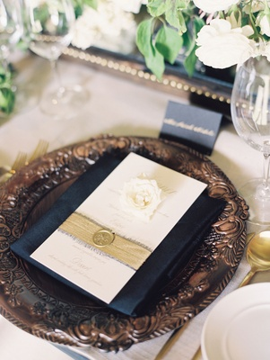 Ivory menu card with frayed gold ribbon and wax seal belly band single gardenia flower on wood