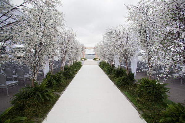 Wedding ceremony white aisle runner greenery and cherry blossom trees on sides silver chairs