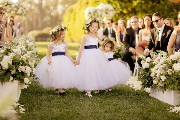 Flower girls holding hands walking down grass aisle flower crown blue sashes gerrit cole wedding
