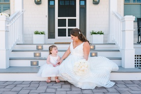 bride in striped hayley paige wedding dress sitting with young flower girl