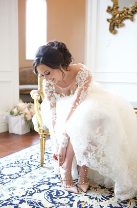 Bride in wedding dress lace illusion long sleeve in chair putting on Valentino pumps studs pink