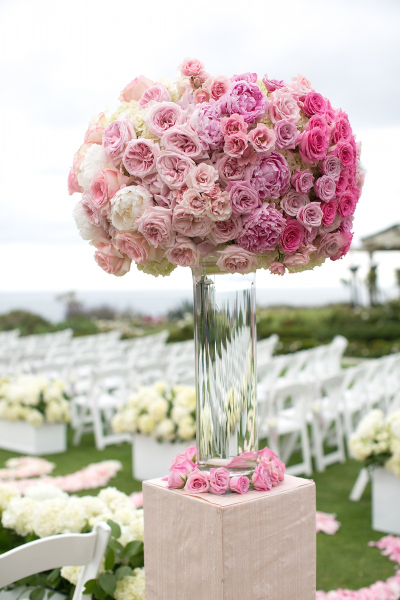 Flower arrangement on riser with pink peonies, pink garden roses