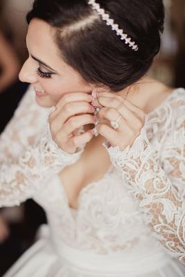 Bride putting on earrings with teardrop pear shape diamond engagement ring  headband sparkle diamond