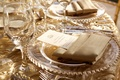 Clear charger plate with gold beads on textured wedding linens