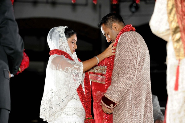 Indian wedding ceremony with red floral garland