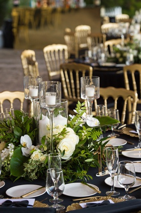 wedding reception centerpiece with white flowers, greenery, and candles
