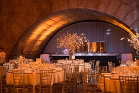 circular tables with white table linens with white floral arrangements of varying sizes