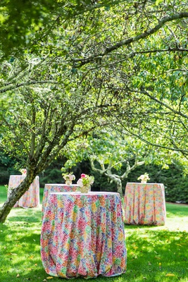 wedding reception outdoor cocktail hour bright multi colored linens on cocktail tables trees