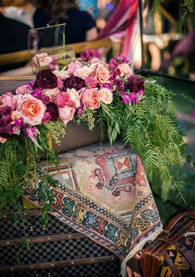 Outdoor bohemian wedding ceremony with tapestry, antique luggage, peach, pink, red roses, greenery