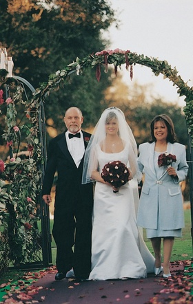 Bride and parents walk through ceremony gate entrance