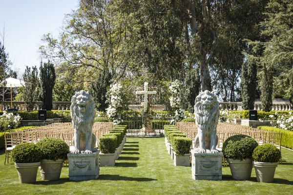 Garden wedding with lion statues and hedges