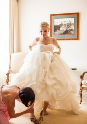 Bridesmaid helping bride put shoes on