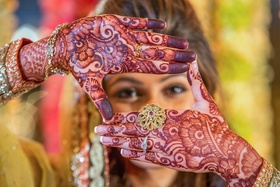 Bride looking through henna hands with intricate ring