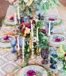 colorful centerpieces with gold and silver candlesticks maroon flowers greenery colored glassware
