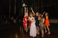 group of women at wedding reception leaping for the bridal bouquet