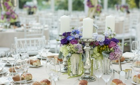 Mercury glass candlesticks next to purple flower centerpiece