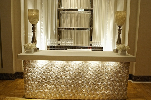 Bar station wrapped with rosette linens and large candleholder