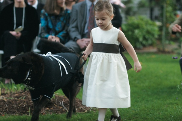 Black dog walks with flower girl down grass aisle