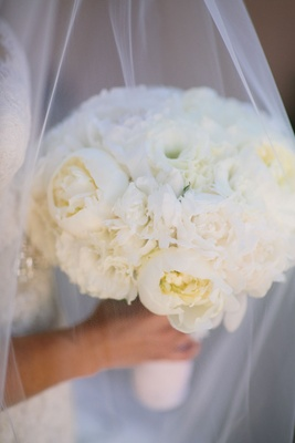 Bride holding wedding flowers of white peonies