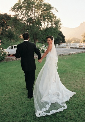 Bride wears cathedral veil with lace on ends
