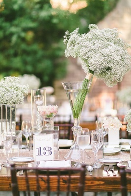 Ranch wedding reception with wood table, white flowers and table number with a golden glitter edge