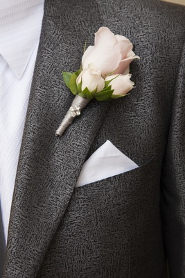 Groom in grey suit with three rose boutonniere