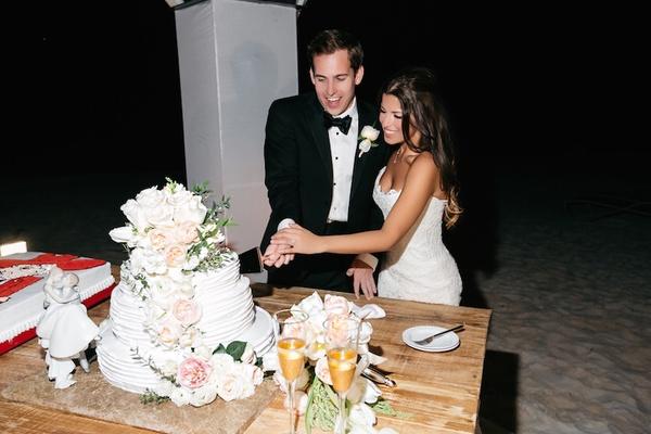 Bride in a strapless Anna Maier ~ Ulla-Maija gown, groom in black tuxedo cut white wedding cake