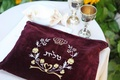 Kiddush cups and maroon velvet embellished with Hebrew