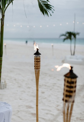 wedding reception on beach in the bahamas tiki flame torches on sand string lights