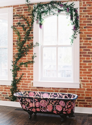Brick wall vine on window black claw-foot bath tub with pink flowers painted rose