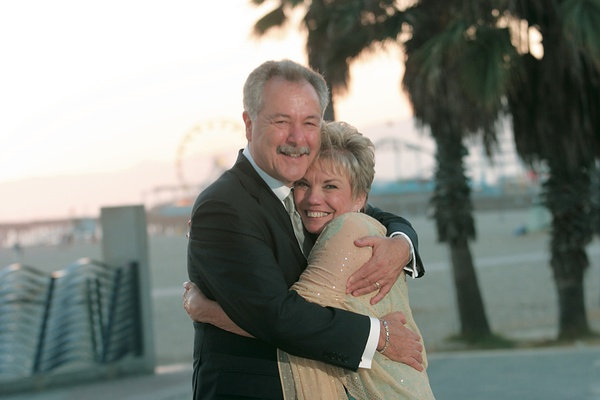 Older couple smiles in front of beach and ferris wheel