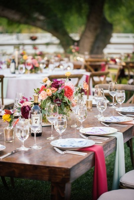 Outdoor bohemian wedding reception bare wood table with draped pink and olive cloth napkins