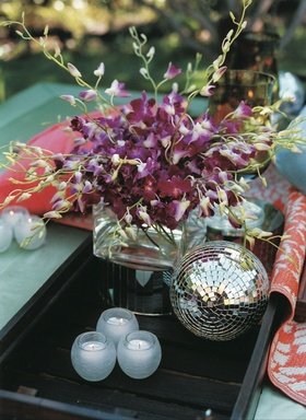 Daybed with black tray, orchid arrangement, and disco ball