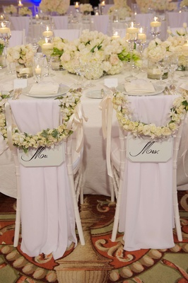 Mr. and Mrs. chairs with white rose decorations