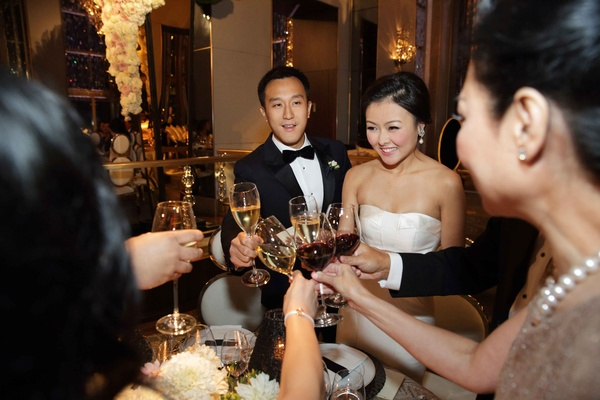 Bride in strapless wedding dress and groom in tuxedo toast champagne and cheers with guests drinking